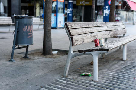 Sabadell, SPAIN - 06/24/2020: garbage on a bench near a paper bin Stockfoto - 150199577