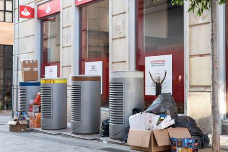 Sabadell, SPAIN - 06/24/2020: trash on the ground around waste containers near Santander Bank office Editorial