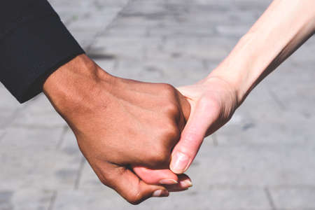 honding hands caucasian and african american women. Concept of multiculturalism and friendship 版權商用圖片