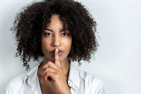 beautiful afro-american woman doing gesture of silence with finger in lips with white background