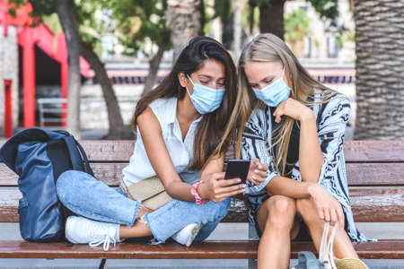 young attractive indian woman showing mobile phone screen to a caucasian friend, both using face masks and sitting on a bench of a park