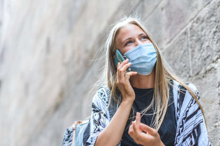Portrait of a beautiful blonde caucasian woman using a blue face mask talking by phone near an ancient building. Copy Space on the left