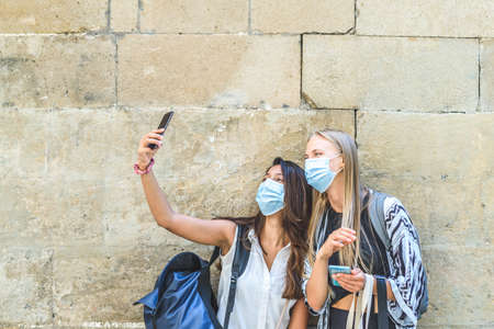 two young beautiful female tourists wearing masks and carrying backpacks doing a self picture in the street near an aged wall