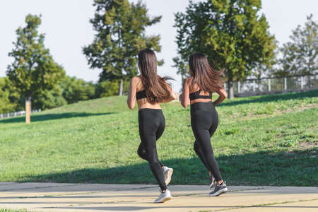 rear view of two young caucasian women with black sport clothes running in a green park 版權商用圖片