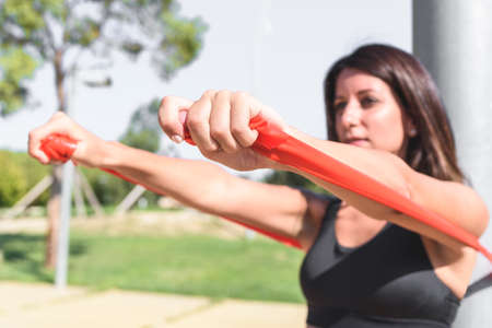 Latin woman exercising using resistance bands with the help of light post on a green park. selective focus on right hand