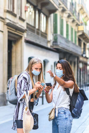 young indian female tourist helping other caucasian tourist to find an address with the help of an smart phone Banco de Imagens