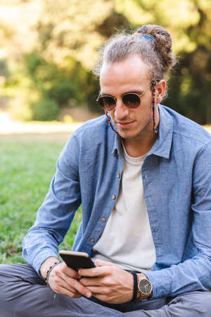 portrait of a caucasian young man dressing causal and protecting from sun with sunglasses sitting on the grass of a green urban park while using an smart phone