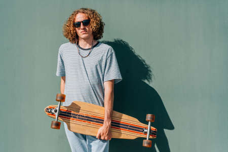 attractive young guy looking at camera with his long board on a sunny summer day Standard-Bild
