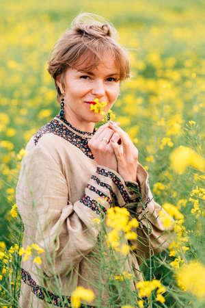 vertical portrait of a beautiful woman on hippie dress smelling rape flower Standard-Bild