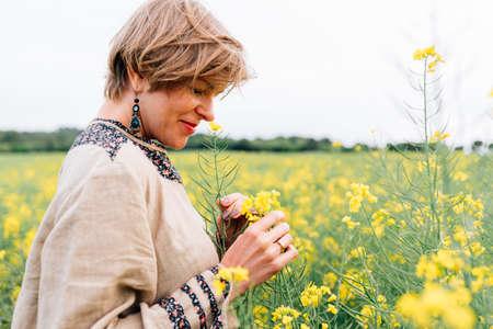 beauty on hippie dress on rape flower field collecting flowers