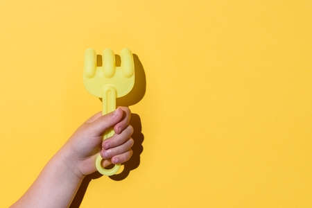 yellow toy rake on the hands of a caucasian boy with yellow background
