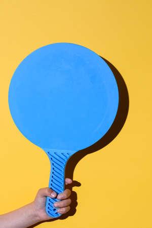 blue beach racket on the hands of a caucasian kid Standard-Bild