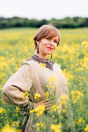 vertical portrait of an attractive woman on a rape flower field Standard-Bild