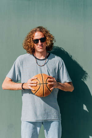 Guy looking at camera with basketball ball on his hands with a green background