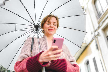 beautiful caucasian woman using her pink phone on a rainy day