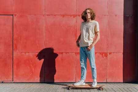 Horizontal portrait of an attractive young man staying on his skateboard Standard-Bild