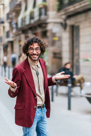 Caucasian young man on the street gesturing with open arms and looking up Standard-Bild