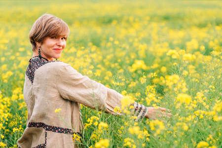 blonde attractive woman walking on a yellow flower field Standard-Bild