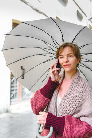 blond young woman with umbrella talking by phone on the street