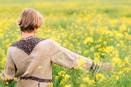 blonde young woman walking on a yellow flower field
