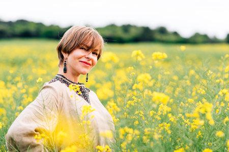 horizontal portrait of an attractive woman on a rape flower field Standard-Bild