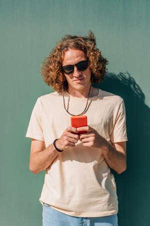 attractive young redhead man using his smart phone near a green wall Standard-Bild