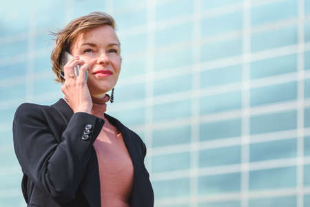 portrait on an attractive blond business woman discussing by phone on the street