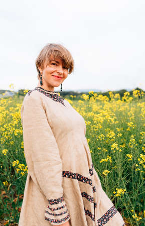 vertical portrait of an attractive woman on a yellow flower field