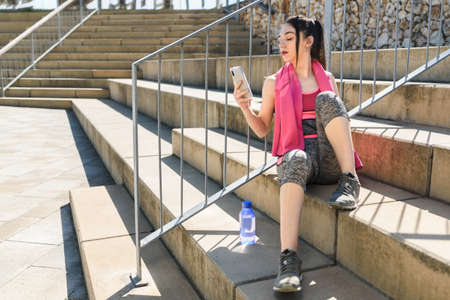 young attractive woman on sport clothes resting and using her phone