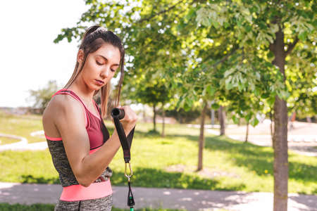 attractive young sportswoman exercising arms with resistance bands in the park