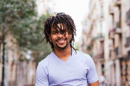 portrait of a latin young man with dreadlocks walking the street in Barcelona