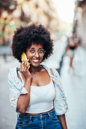 vertical portrait of an african woman looking at camera while talking by phone Standard-Bild