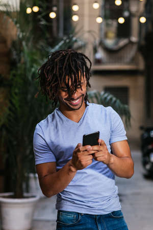 vertical portrait of a young latin man using his phone in the streets at evening