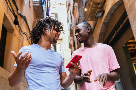 latin and african friends commenting about social networks content on the phone and smiling