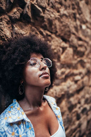 vertical portrait of an attractive african woman with closed eyes leaning on stone wall