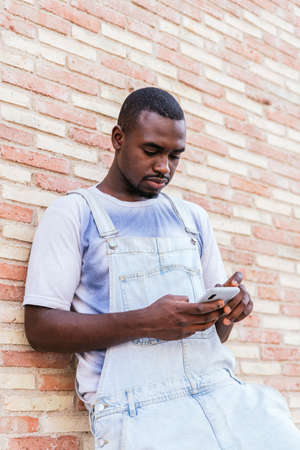 young african man leaning on a brick wall and using his smart phone Standard-Bild