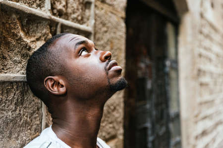 Portrait of a thoughtful young african man leaning on a wall and looking up