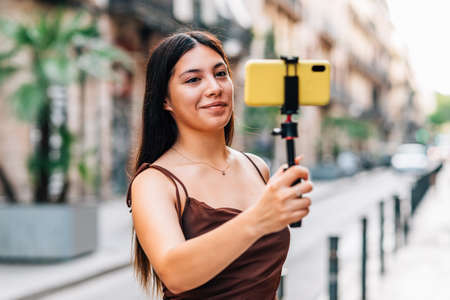 young chinese woman live streaming with her phone in the streets of Barcelona Standard-Bild
