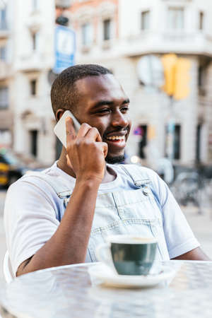 Attractive african man taking by phone on a bar terrace Standard-Bild