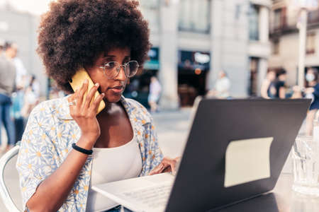 african woman working remotely from the terrace of a bar Standard-Bild
