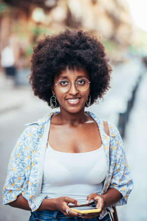 vertical portrait of an african woman looking at camera while holding her phone Standard-Bild