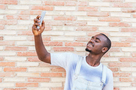 young afro american man taking himself a picture with a brick wall as background