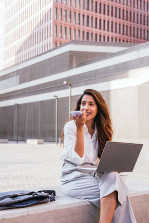 Stylish young business woman sitting outdoors with a laptop and sending voice message with phone Standard-Bild