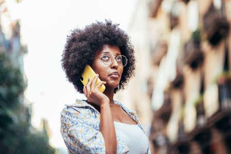 portrait portrait of an african woman talking by phone on the street Standard-Bild
