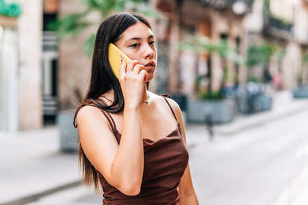 attractive chinese woman talking by phone in the city streets