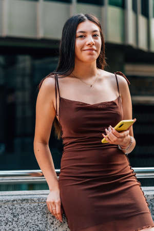 chinese young woman holding a yellow phone in the street and smiling to camera