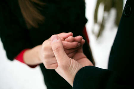 tenderly: young couple tenderly holding hands. hands closeup. Stock Photo