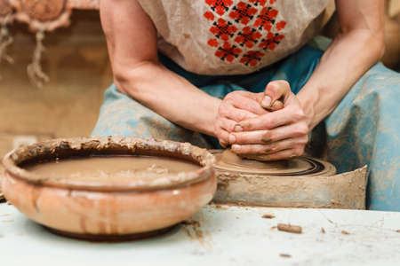craftswoman: hands of a potter, creating an earthen jar on the circle. Potters wheel. Horizontal. Hands working on pottery wheel