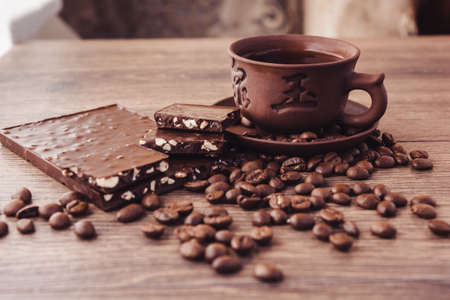 roasted coffee beans with chocolate and nuts on a wooden surface.