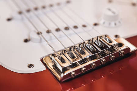 Part of modern electric six string guitar red color with glossy finish, pickups and control knobs isolated on wooden background close up view.